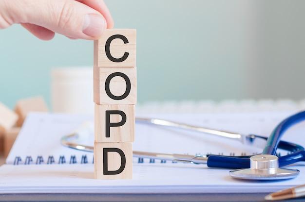 Mano d'uomo che tiene un cubo con la lettera c dalla parola bpco scritta su cubi di legno vicino a uno stetoscopio su uno sfondo di carta, concetto medico, bpco - malattia polmonare ostruttiva cronica