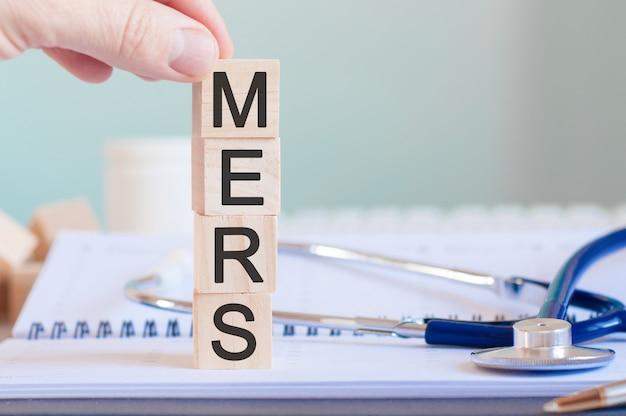 Mano d'uomo che tiene un cubo con la lettera m dalla parola mers scritta su cubi di legno vicino a uno stetoscopio su uno sfondo di carta, concetto medico