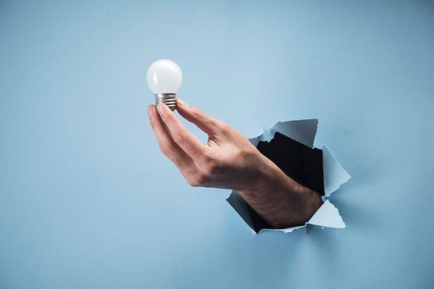 Mano d'uomo che tiene una lampada su una scena blu