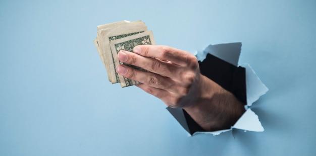 Mano dell'uomo che tiene soldi sulla scena blu