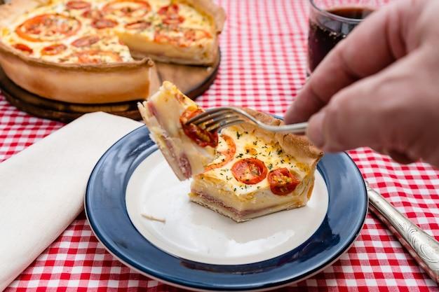 Una mano d'uomo che tiene un pezzo di prosciutto e fetta di torta di formaggio o quiche loraine su una forchetta. cibo domestico, concetto sano