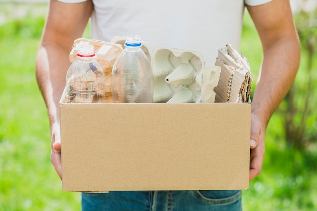 La mano dell'uomo che tiene i prodotti di riciclaggio nella scatola di cartone