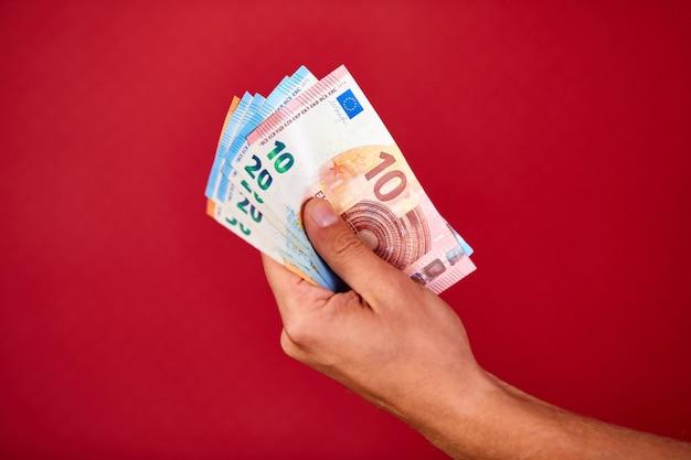 Mano d'uomo tenendo e mostrando unione europea banconota euro soldi isolati su sfondo rosso, indoor, studio shot, copia dello spazio