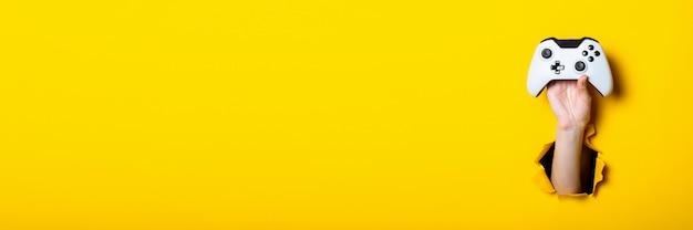 Mano d'uomo che tiene un bastone su uno sfondo giallo brillante
