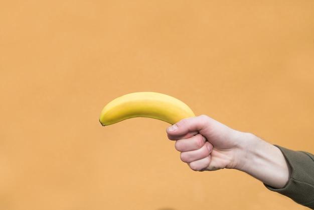 La mano dell'uomo tiene una banana su una parete arancio. copyspace