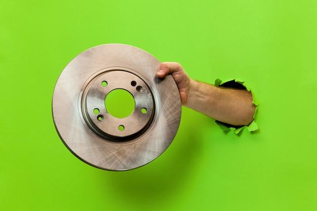 La mano di un uomo tiene un disco del freno dell'auto attraverso carta verde strappata. mano attraverso carta verde strappata