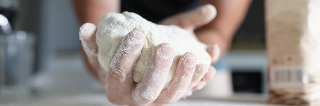 La mano dell'uomo tiene l'impasto sul tavolo dove la farina è sparsa