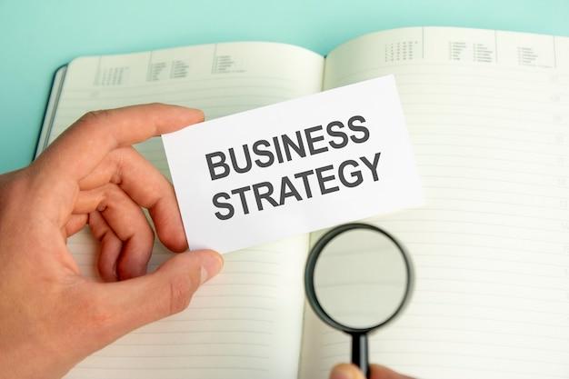 La mano di un uomo tiene una carta bianca con il testo strategia aziendale sopra un taccuino di carta aperto e una lente d'ingrandimento in una cornice nera
