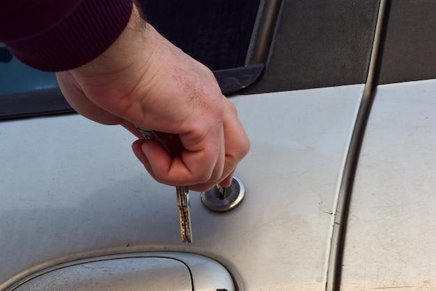 La mano di un uomo inserisce una chiave nel buco della serratura di una portiera di un'auto usata. ci sono diverse chiavi in mano.