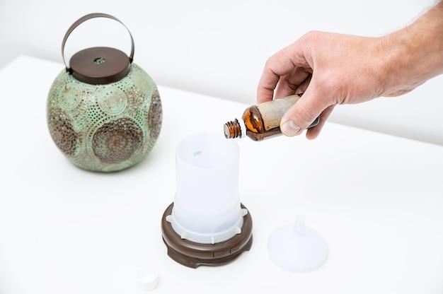 La mano dell'uomo sta riempiendo d'acqua una capacità di diffusore di aromi.