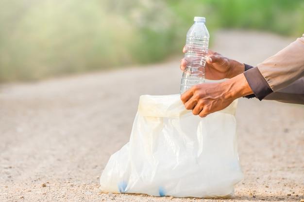 La mano dell'uomo sta prendendo una bottiglia di plastica.