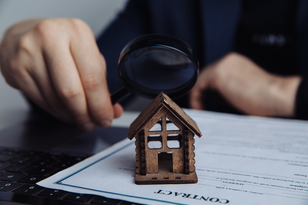Mano d'uomo, lente d'ingrandimento e casa. concetto di affitto, ricerca, acquisto di immobili.