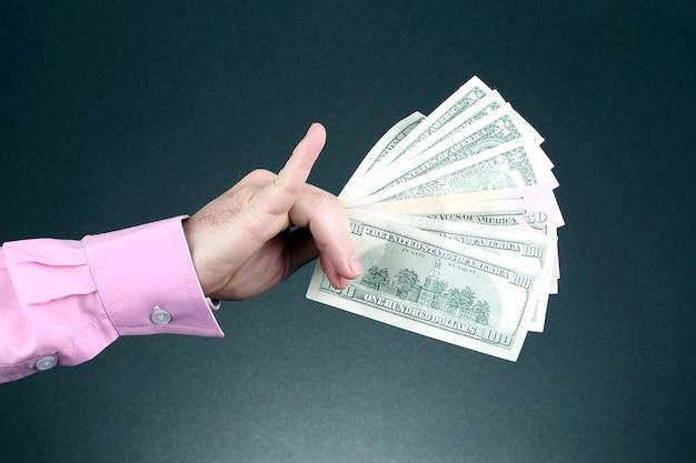 Mano d'uomo in una camicia rosa con banconote da un dollaro
