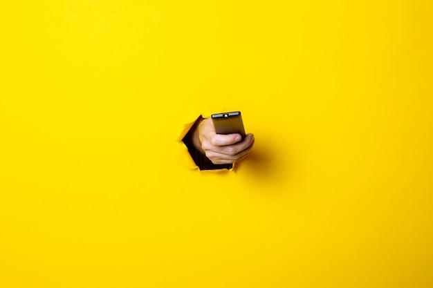 La mano dell'uomo spinge il pulsante sul telecomando della tv su uno sfondo giallo brillante