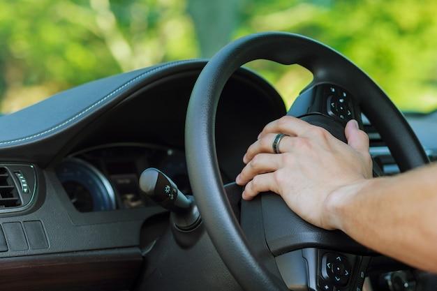Mano d'uomo sul volante di un'auto con conducente della ruota dell'auto