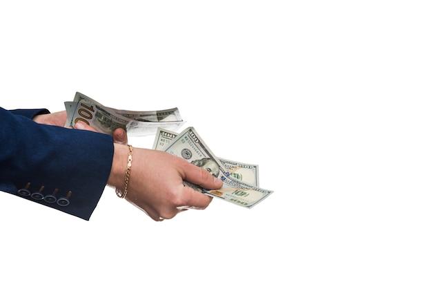 Mano d'uomo in tuta dandoci dollaro isolato sul muro bianco. avvicinamento.