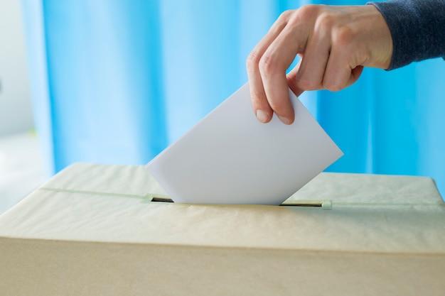 La mano dell'uomo lancia una scheda elettorale per votare in un seggio elettorale durante le elezioni.