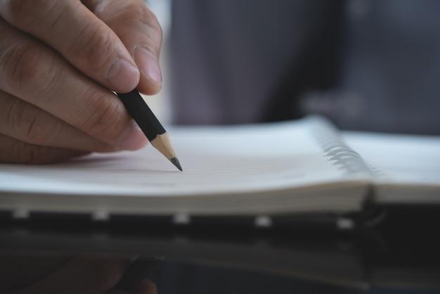 Mano dell'uomo con la matita scrivendo sul taccuino