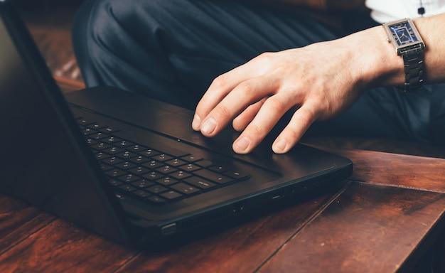 La mano di un uomo con un orologio da polso si trova sul touchpad del laptop.
