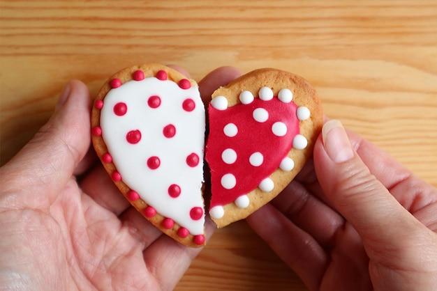 La mano dell'uomo e la mano della donna che tengono due biscotti a forma di mezzo cuore si attaccano su sfondo di legno