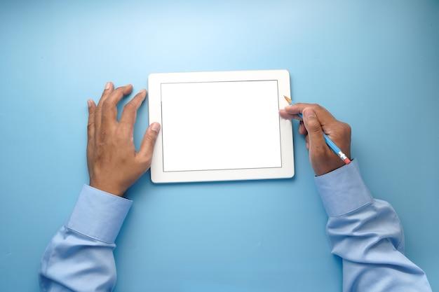 Mano d'uomo lavorando sulla tavoletta digitale sulla scrivania in ufficio