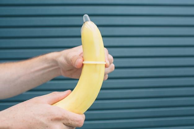 Le mani dell'uomo tengono in mano una banana con un preservativo elastico. isolato su strisce