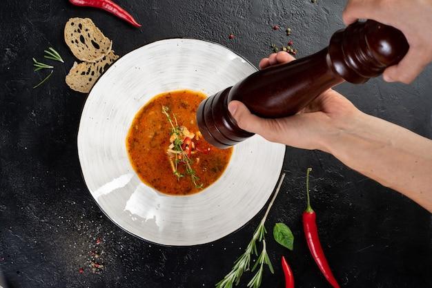 Le mani dell'uomo tengono una lista dei peperoni sopra un piatto con la minestra.