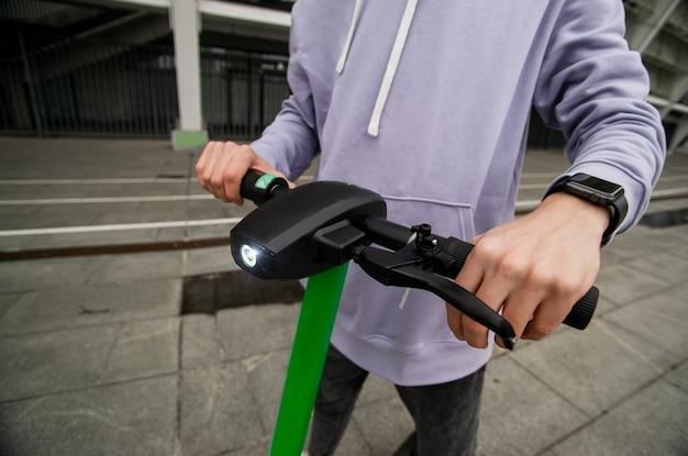 Le mani dell'uomo tengono il volante dello scooter elettrico. concetto di guida facile. ragazzo in felpa con cappuccio grigia casual ha noleggiato un veicolo elettrico per viaggiare in città. concetto di trasporto ecologico.
