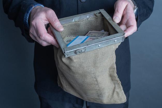 Mani dell'uomo che tengono una borsa della banca piena di soldi.