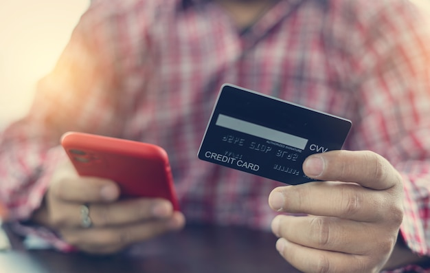 Mani dell'uomo che tiene una carta di credito e utilizzando smart phone per lo shopping online. carta di credito per pagare e fare acquisti online. concetto di pagamento online. libero professionista in caffetteria e lavora.