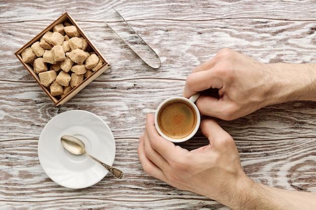 Mani dell'uomo che tiene tazza di caffè sul tavolo di legno