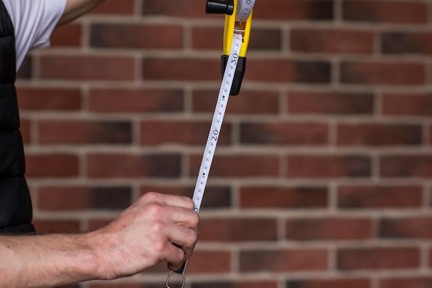 Le mani dell'uomo che tengono il righello in centimetri di lunghezza per l'uso edilizio contro il muro di mattoni rossi. copia spazio. il fuoco è al righello. concetto di edificio.