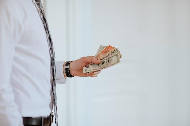 Mani dell'uomo che tengono soldi come euro e dollari su sfondo bianco.