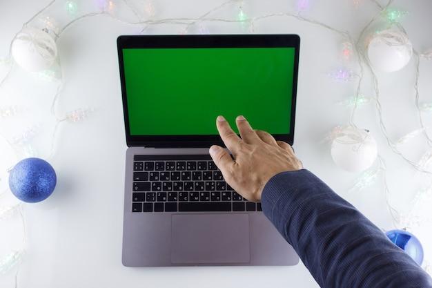 Le mani di un uomo e un laptop con uno schermo verde