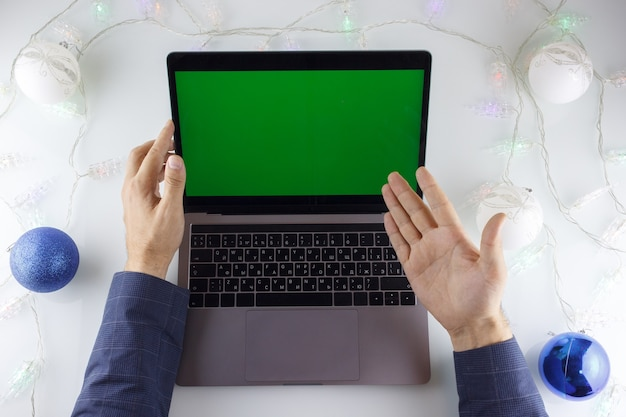 Le mani dell'uomo indicano un laptop con uno schermo verde