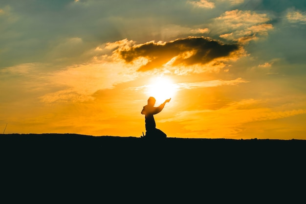Le mani dell'uomo pregano per la benedizione di dio sullo sfondo del tramonto