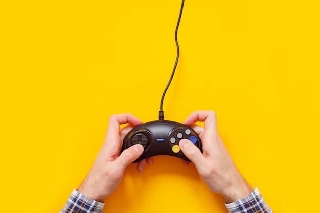 Mani dell'uomo con il vecchio gamepad cablato isolato su giallo