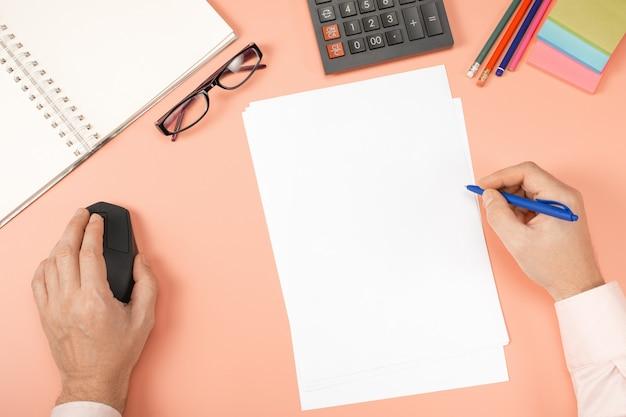 Mani dell'uomo che lavorano con computer pc e calcolatrice, taccuino, penna, mouse, computer sul moderno tavolo da scrivania rosa in ufficio.