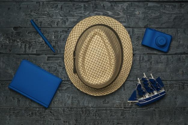 Un cappello da uomo, un modellino di una nave, una macchina fotografica e un taccuino su un tavolo di legno. il concetto di pianificazione del viaggio.
