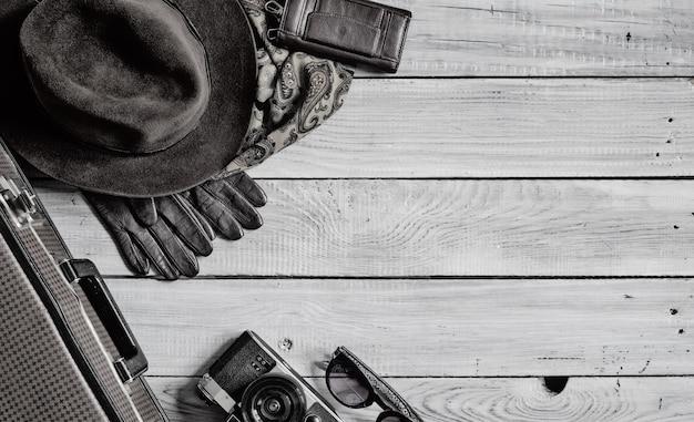 Cappello da uomo e accessori retrò per viaggiare su una superficie in legno verniciato bianco