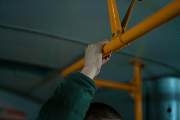 Un uomo tiene una maniglia su un treno della metropolitana. in piedi nel trasporto pubblico e tiene il corrimano