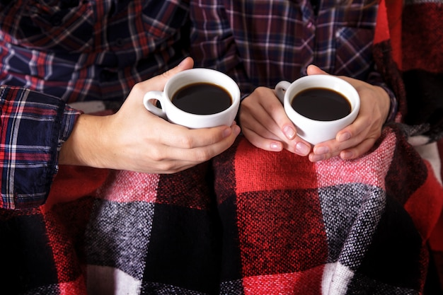 Le mani dell'uomo e della donna tengono due tazze di caffè nel plaid a forma di verme.