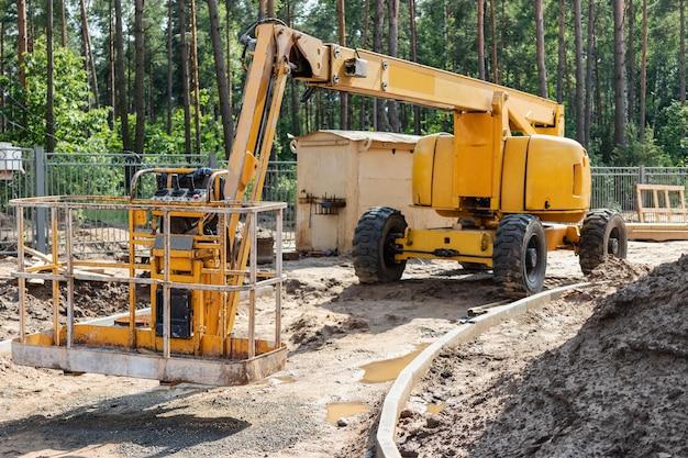Il lavoro dell'uomo è all'altezza. meccanismo di costruzione semovente per sollevare i lavoratori ad un'altezza in un cantiere edile. lavoro sicuro al top.