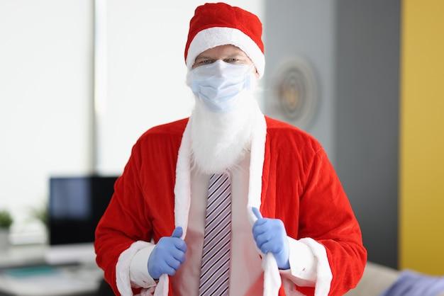 Uomo in costume di babbo natale e maschera medica protettiva.
