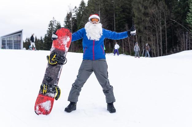 Uomo in cappello di babbo natale con uno snowboard in una stazione sciistica.