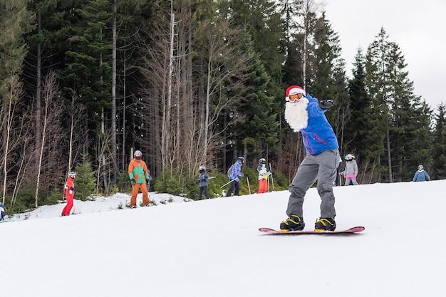 Un uomo con un cappello da babbo natale con lo snowboard in una stazione sciistica.