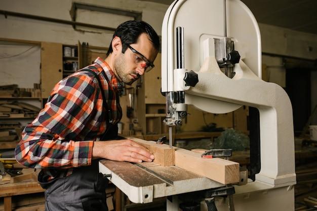 Uomo che sega una tavola di legno su una sega a nastro