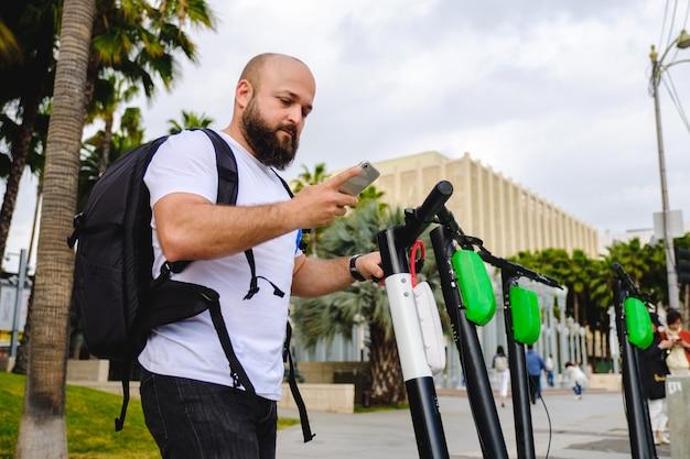 Uomo scansione codice qr con il suo telefono per il noleggio di scooter elettrici