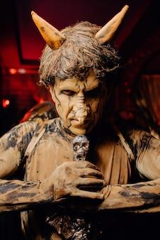 Uomo in un costume spaventoso e trucco a una festa di halloween