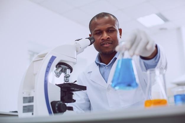 Uomo di scienza. biologo esperto ispirato che lavora con il suo microscopio e tiene in mano un tubo